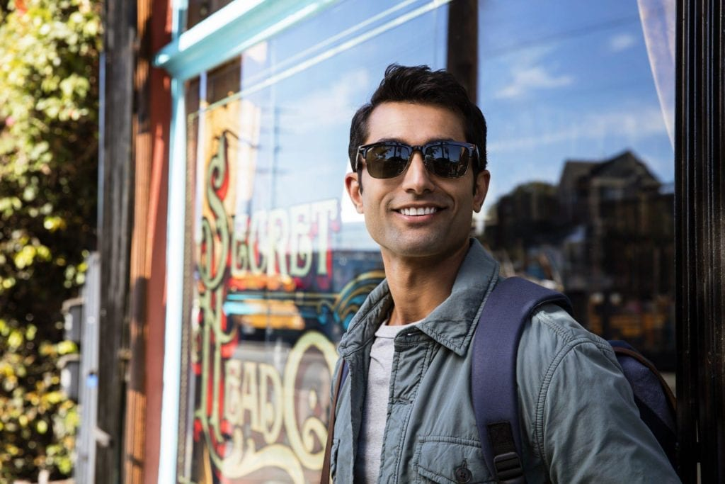 Smiling young man outside a cafe wearing sunglasses and Invisalign clear aligners Montrose